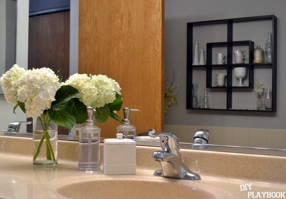 These bathroom accessories and fresh flowers are sophisticated and sleek.