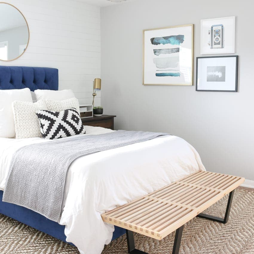 Bright bedroom with soft grey walls and bright blue accents.