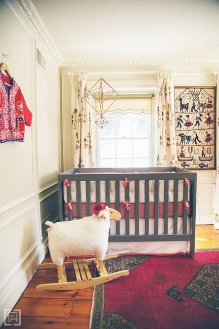 This hippie style nursery is cute with a pink rug and fun wall art.