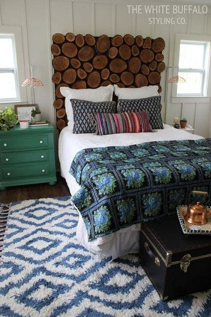 This guest room is rustic with a log headboard and patterned rug.