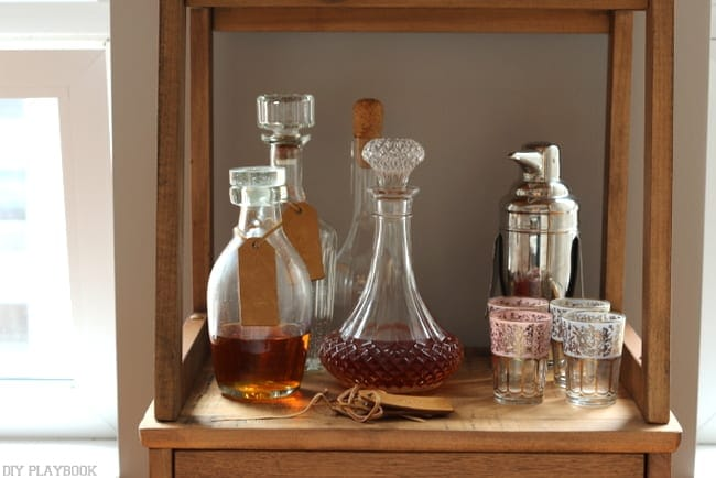 A cute bar shelf with a crystal decanter is a great living room accent.
