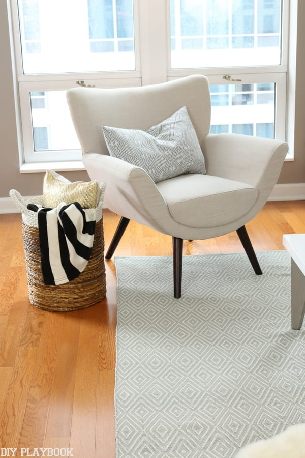 Welcoming greige armchair with a basket of throws and pillows include a black and white striped throw.
