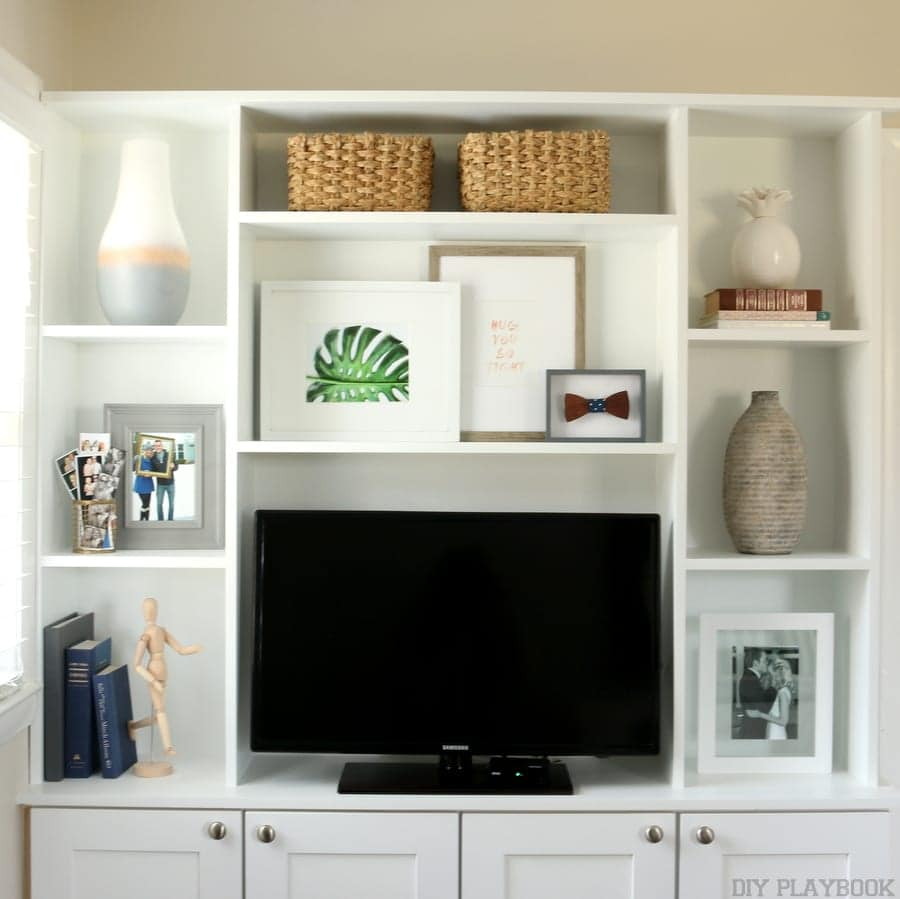 Entertainment center with gallery wall artwork and home accessories.