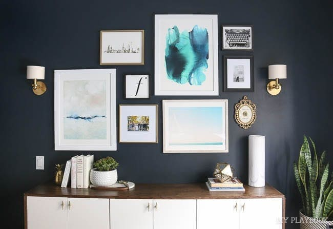 This gallery wall in the guest room looks great against the navy wall.