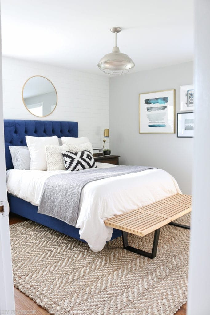 Bedroom with herringbone rug, white pillows and bright blue headboard.