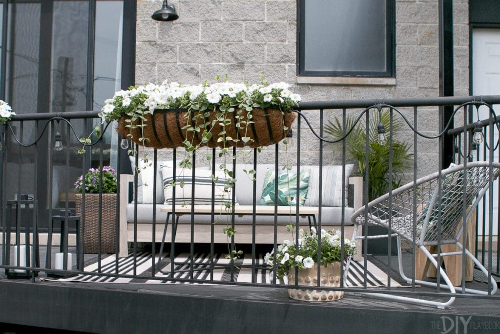 Add hanging flower boxes to a city balcony space