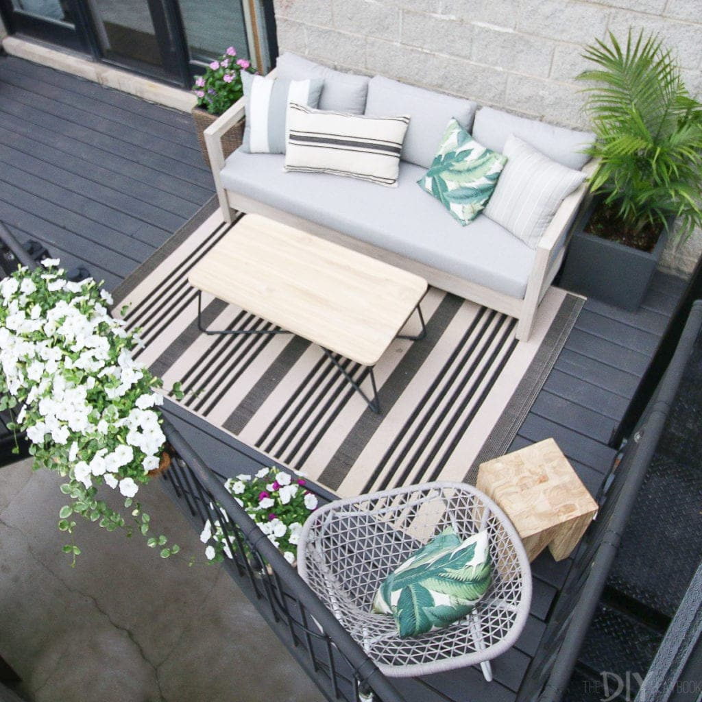 Small city patio makeover with a sofa, coffee table, and chair
