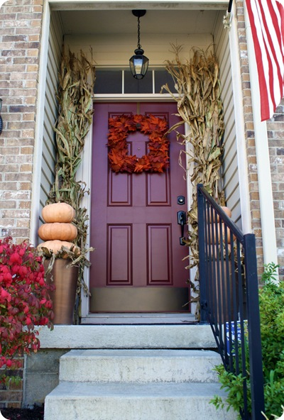 Cornstalks, a wreath, and some pumpkins are all you need to create this front door. Found on Thrifty Decor Chick.