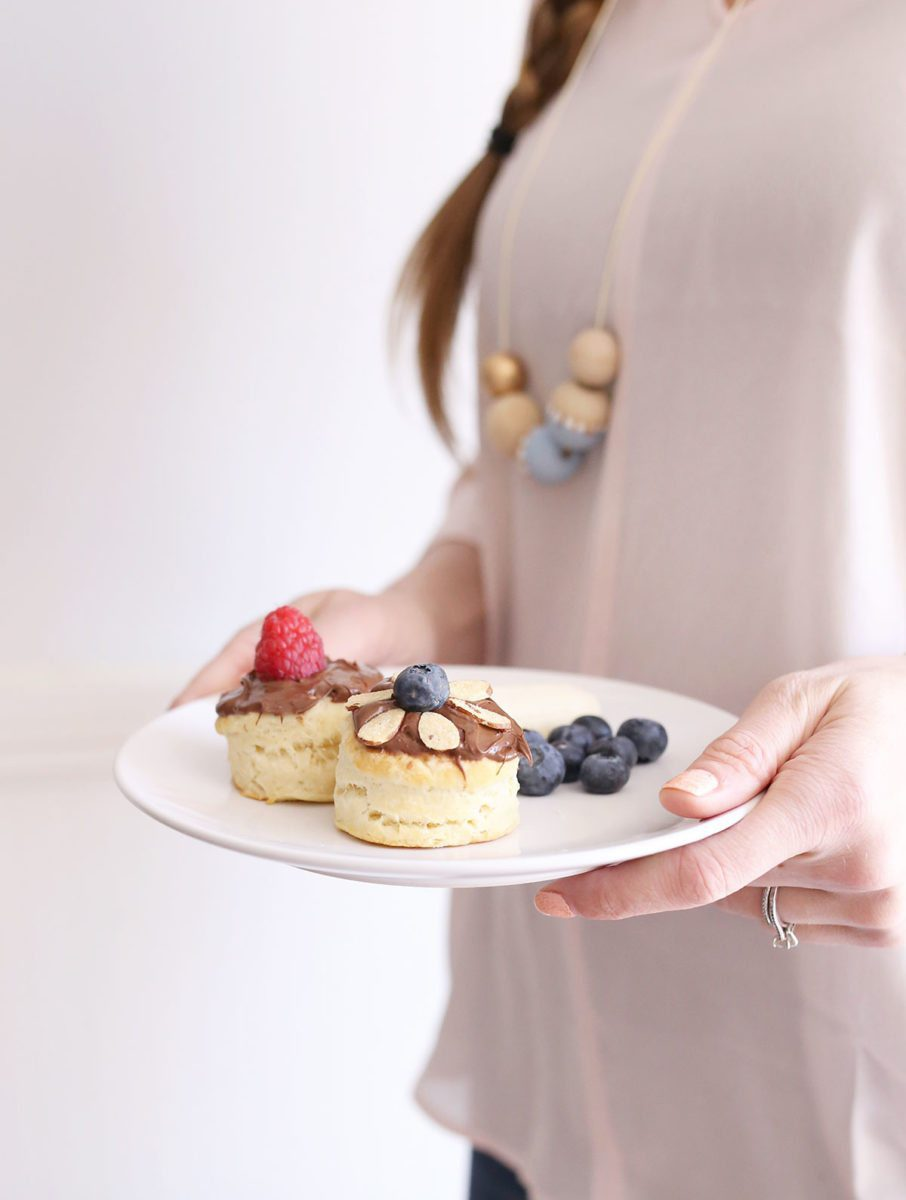 Hands holding plate with two biscuits with Nutella and fruit