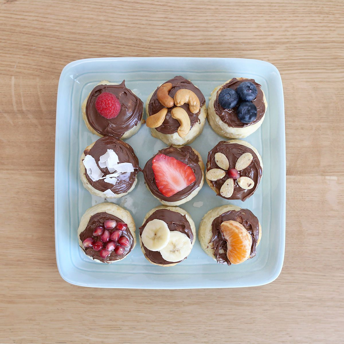 Plate of biscuits with fruit and Nutella on top