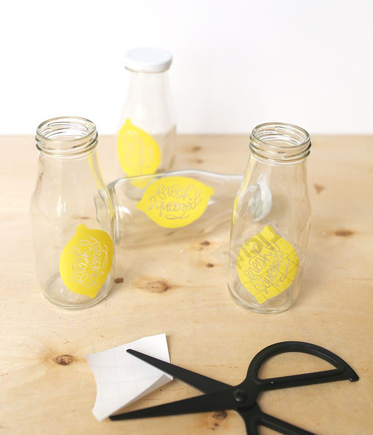 Bottle lids and glass milk bottles with handmade DIY vinyl lemon decals on a wooden background