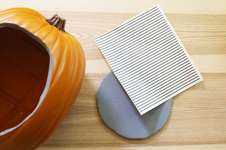 Cutting out vinyl lines with a Cricut machine to apply to foam insert for diorama pumpkin
