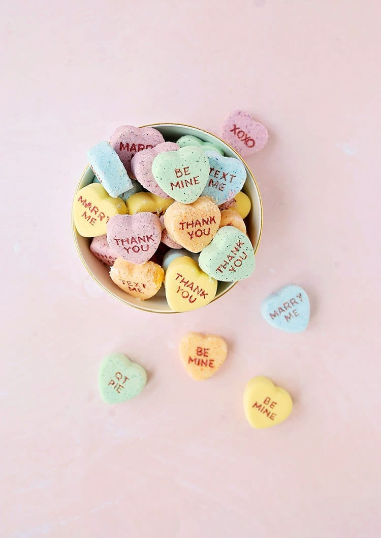 Yellow, orange, blue, and green conversation heart Valentine's Day bath bombs in a bowl on a pink background