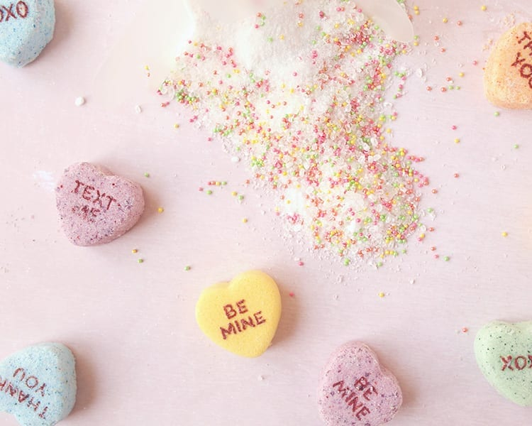 Conversation hearts Valentine's Day bath salts with colorful sprinkles spilled onto a pink background with giant conversation hearts