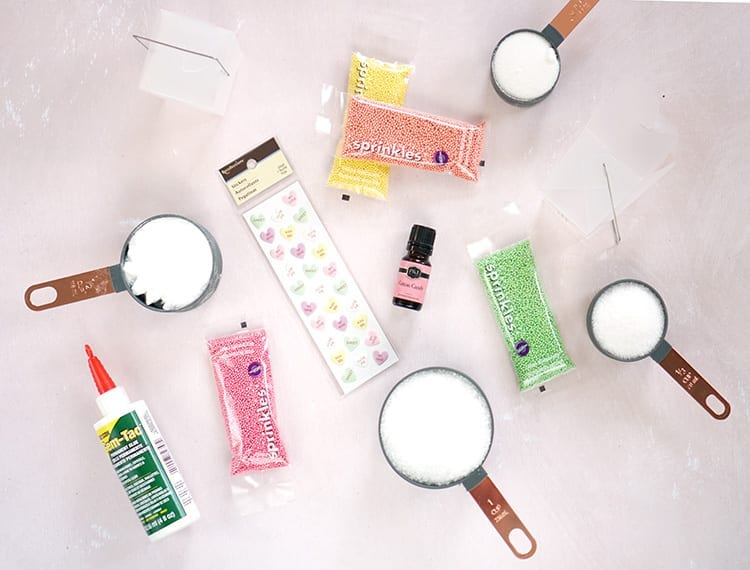 Colorful sprinkles, conversation hearts stickers, measuring cups full of white powder ingredients, and glue on a pink background