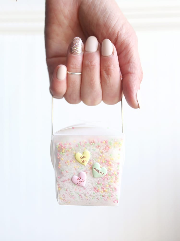 Caucasian hand holding a clear takeout container of conversation hearts Valentine's Day bath salts