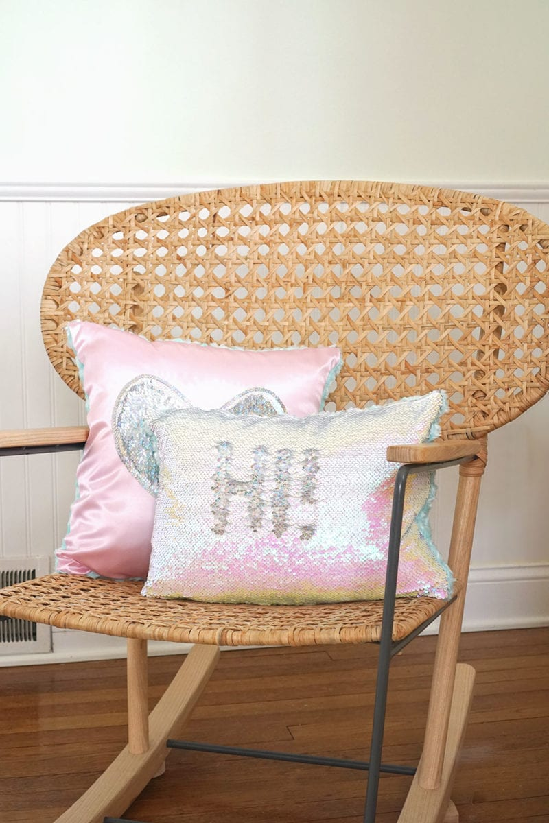 Pink heart magic sequin pillow and iridescent mermaid sequin pillow on wicker rocking chair