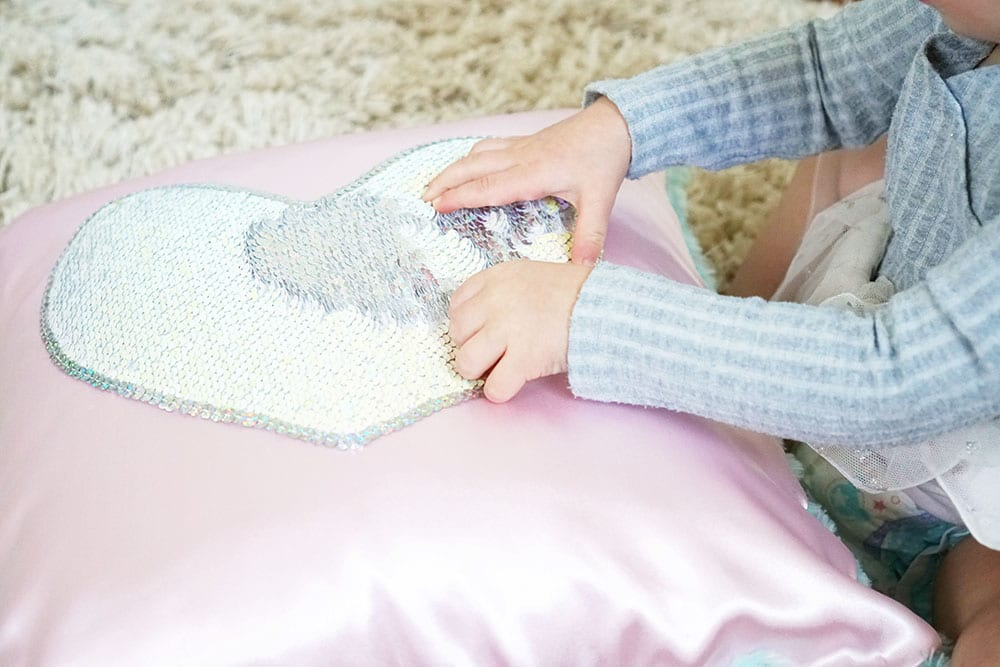 Toddler hands playing with a pink heart shaped magic sequin pillow