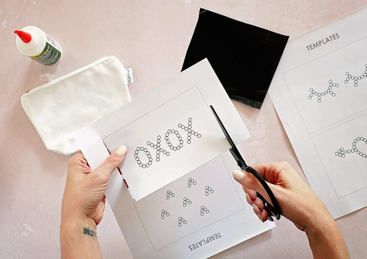 Caucasian hands cutting out an XOXO template from white paper with black scissors against a pink background