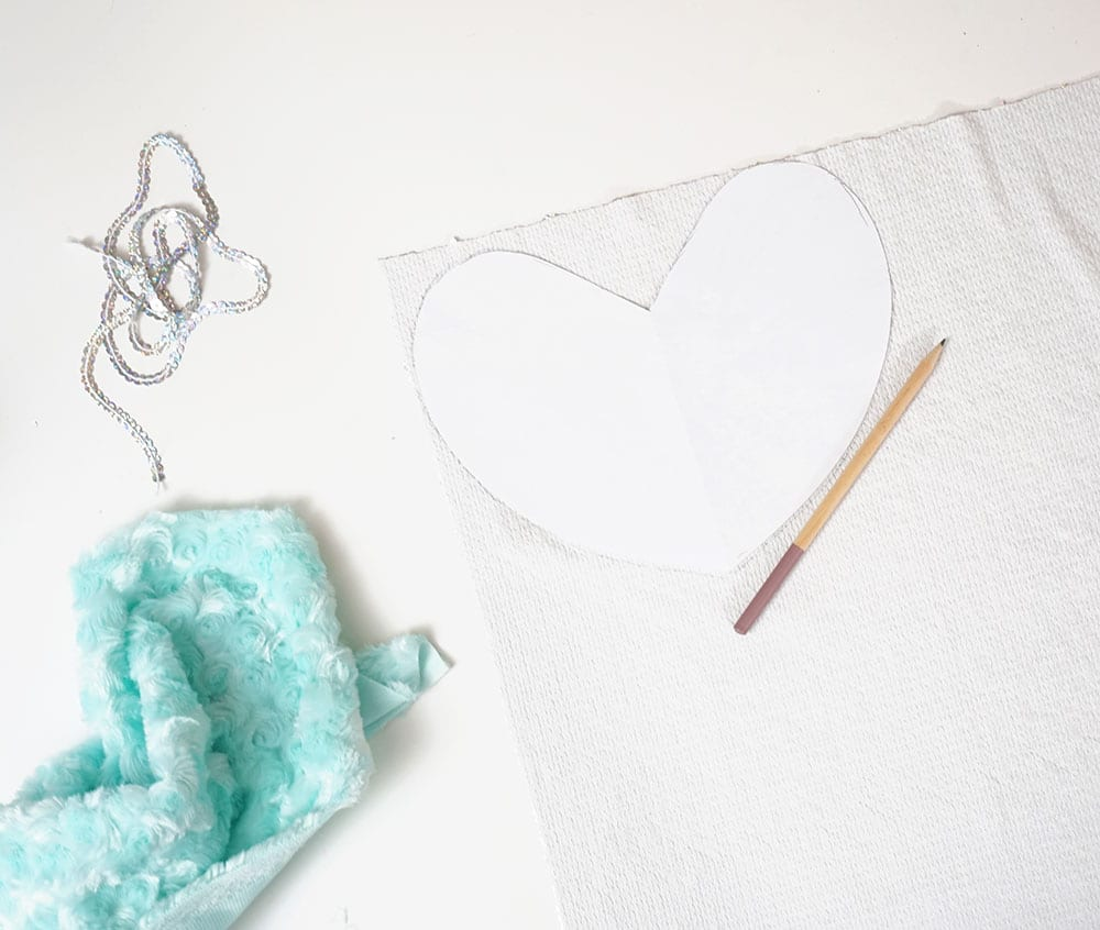 Paper heart and pencil on top of flip sequin fabric next to turquoise faux fur and a strip of sequin trim for a flip sequin pillow