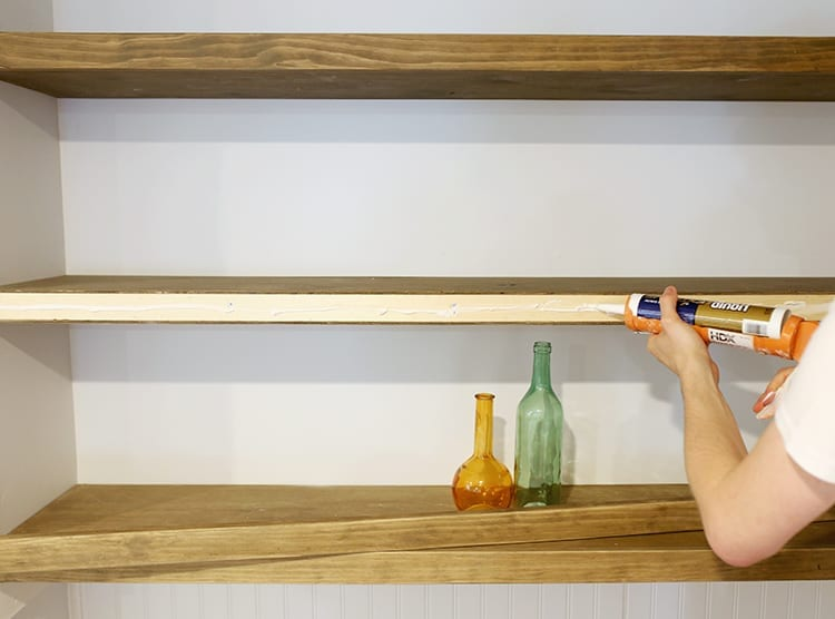 Man gluing the front of a floating shelf against a very light blue wall