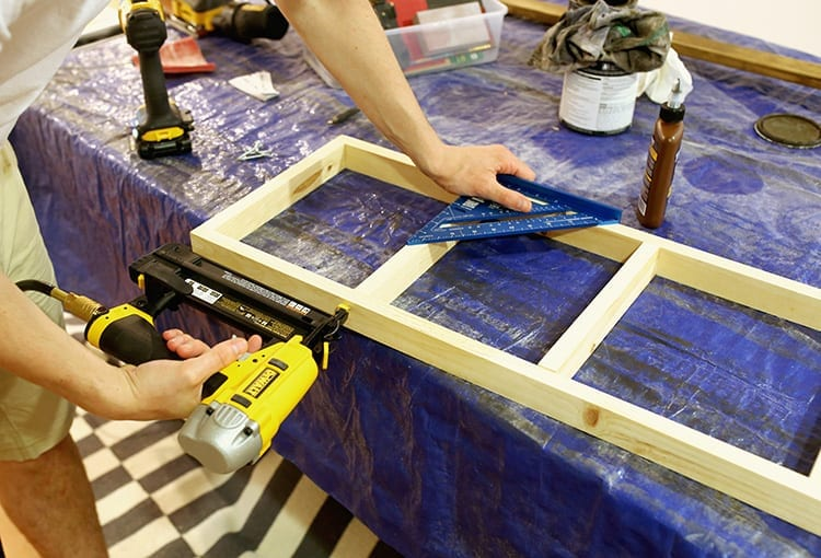 Caucasian hands drilling a screw into a wooden shelf frame on a table covered in a blue tarp