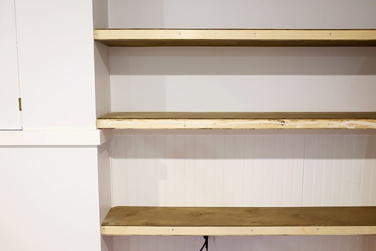 Floating shelves being built and installed against a very light blue wall