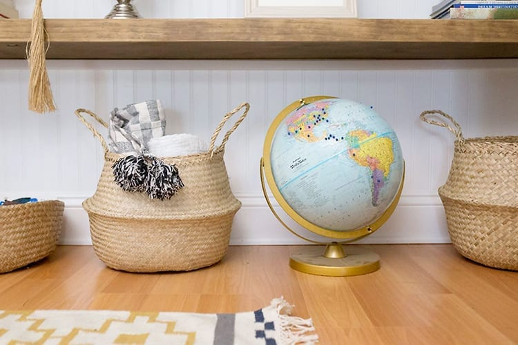 Baskets and globe on wooden floor in front of yellow and white geometric-patterned rug