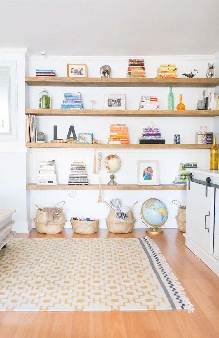 Wall of wooden floating shelves with books and knick knacks on them. Baskets and a globe on the floor in front of a yellow and white patterned rug.