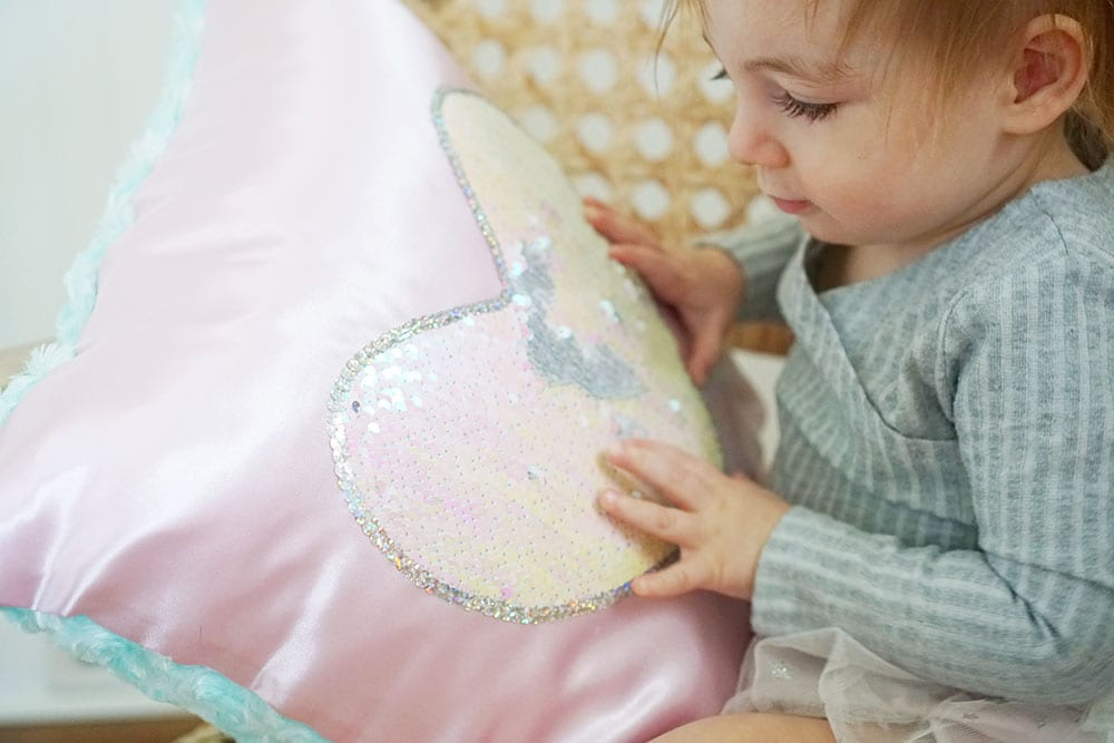 Toddler hands playing with a pink heart shaped flip sequin pillow