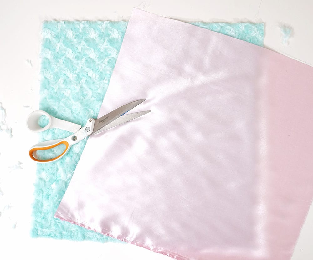 Sewing scissors on top of magic sequin pillow supplies: pink satin and turquoise faux fur fabric squares on a white background