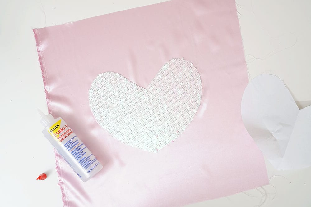 Bottle of Beacon Adhesives Fabri-Tac glue on top of a mermaid sequin fabric heart and pink satin to make a magic sequin pillow