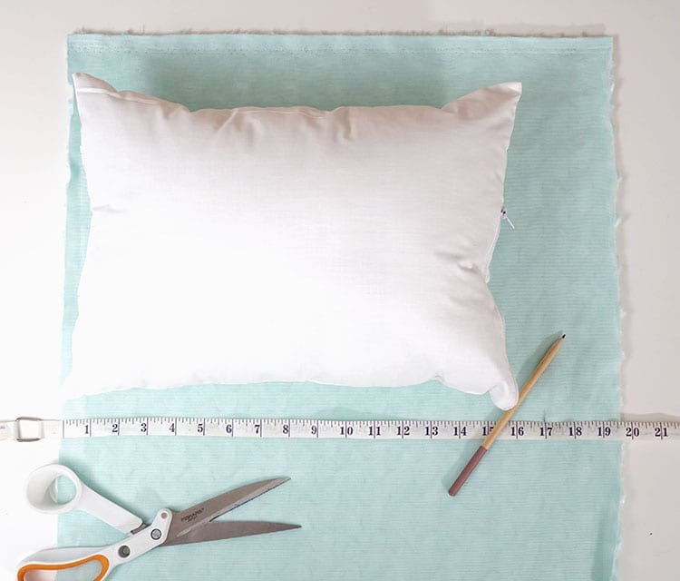 Sewing tape measure and pencil on turquoise fabric for making a magic sequin pillow