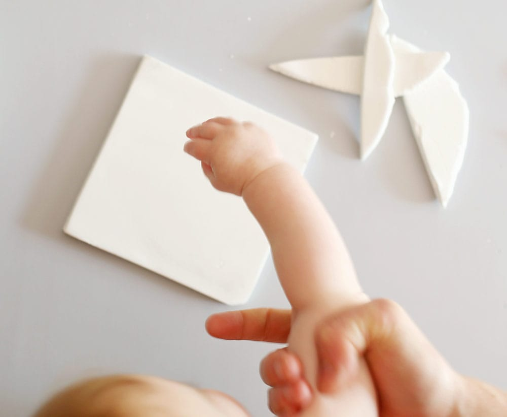 Father holding baby's arm over air dry clay on a silicone baking mat to make a diy baby clay handprint keepsake frame