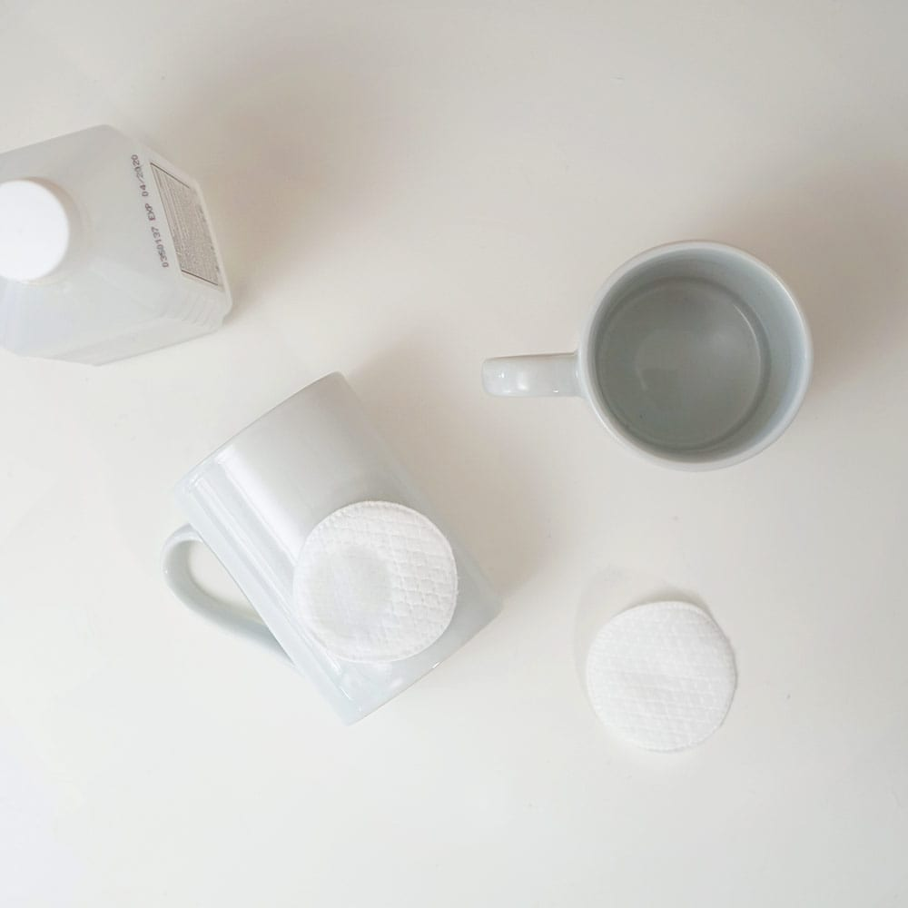 White mugs and cotton pads on a white background