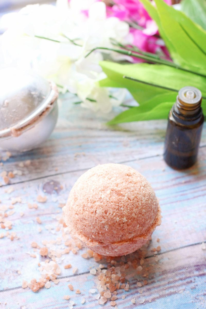 Recipe for pink Himalayan salt bath bombs on a wooden background with an essential oil bottle