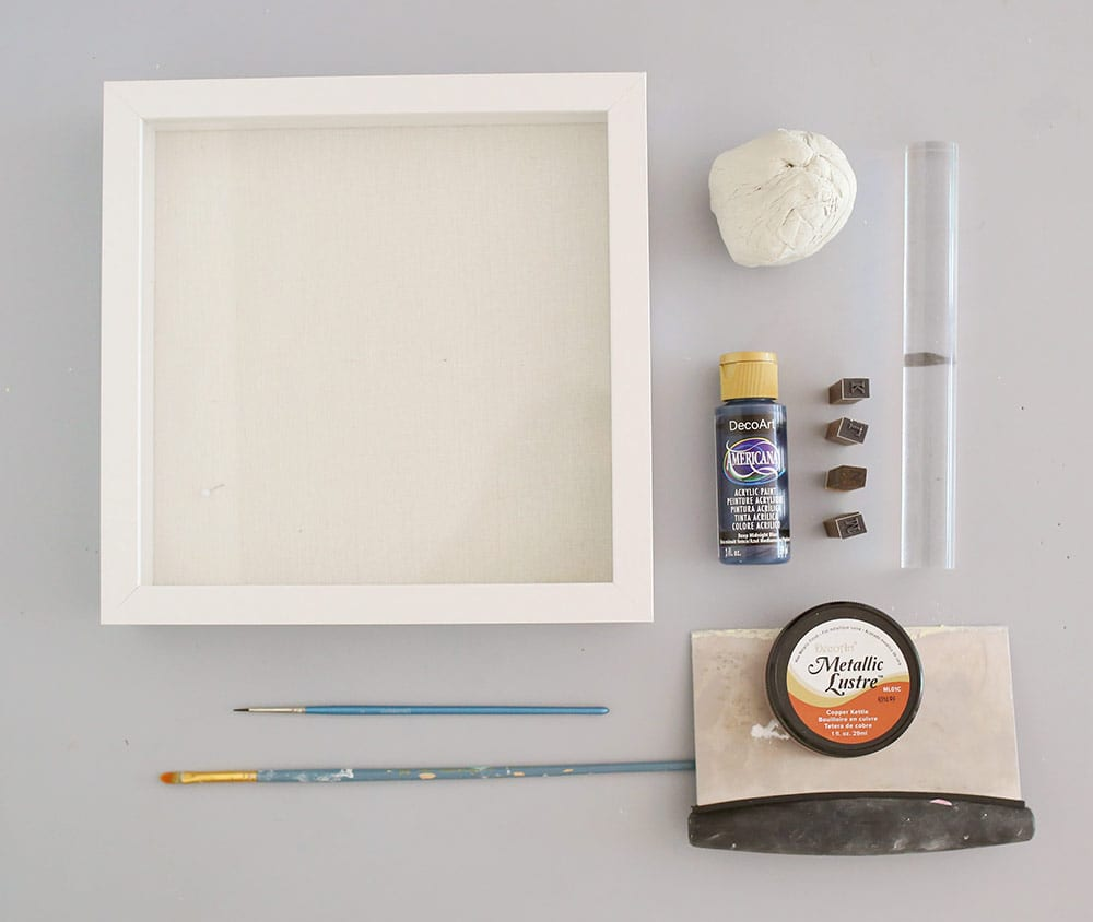 Supplies for an air dry clay on a silicone baking mat to make a diy baby clay handprint keepsake frame