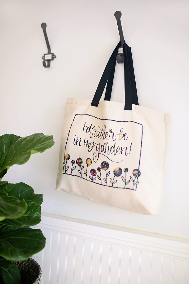 Gardener tote bag made with Cricut Infusible Ink Transfer Sheets hanging on a wall hook with a straw hat and fiddle leaf fig tree