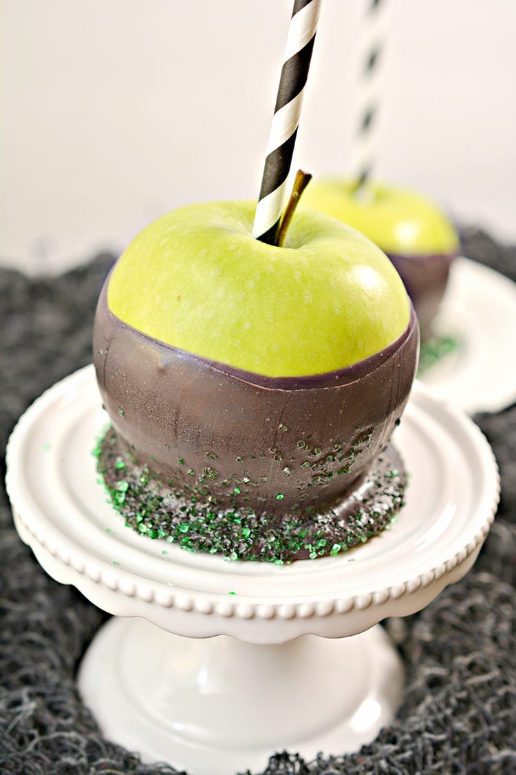 Green apples dipped in black chocolate to make poison apples for a Halloween party