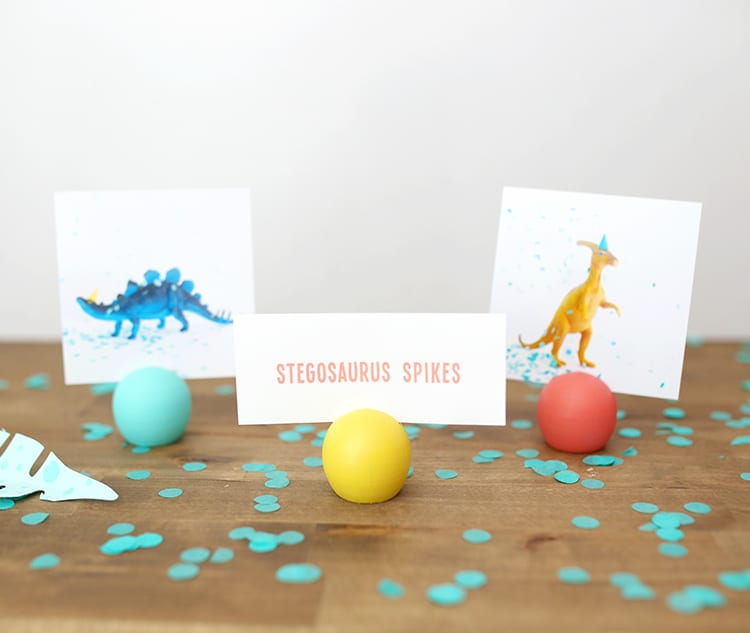 Three colorful wooden DIY place card holders with pictures from a dinosaur party