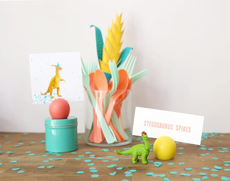 DIY place card holder at a dinosaur birthday party setup with yellow, coral, and teal accessories